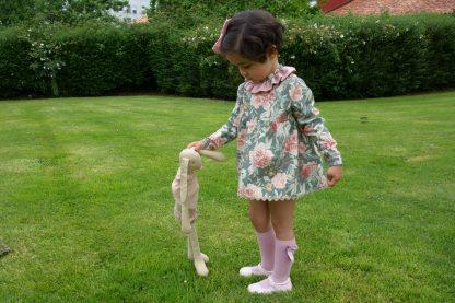 Niña vestida con un conjunto verde estampado flores en un jardin jugado con muñeca. Modelo Garden.