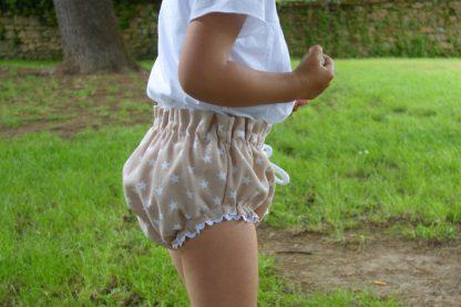 Busto de niña con culotte estrellas beige en un prado.