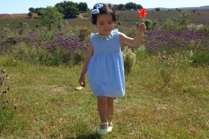 Niña en el campo que lleva puesto vestido plumeti azul con detalles en amarillo.