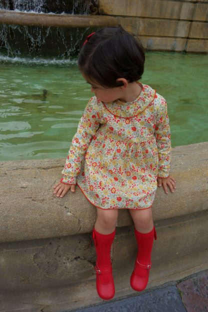 Niña sentada al borde de una fuente con jesusito estampado liberty, modelo Scarlett.