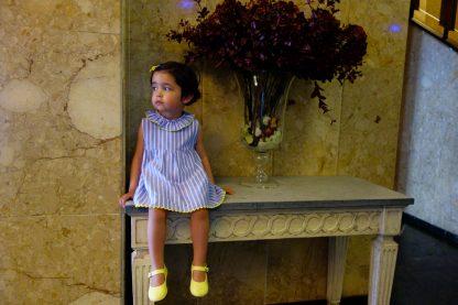 Niña sentada en un recibidor vestida con conjunto blusa rayas azules con detalles amarillos.