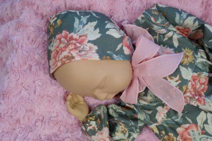 Imagen frontal maniqui bebe con jesusito y capota en verdes y rosa empolvado.