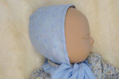 Vista perfil de maniqui bebe con capota azul.