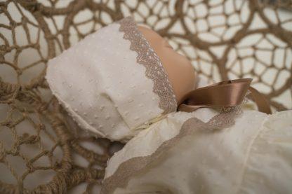 Vista perfil de maniqui con capota plumeti marfil y detalles color topo.