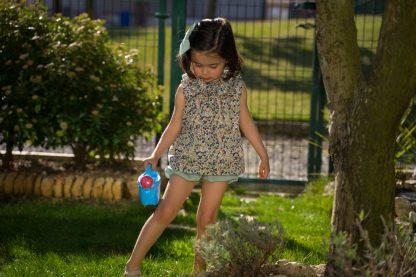 Niña en jardín regando vestida con blusa sin mangas liberty en tonos verdes y bombacho verde.Lleva lazo en el pelo color verde.
