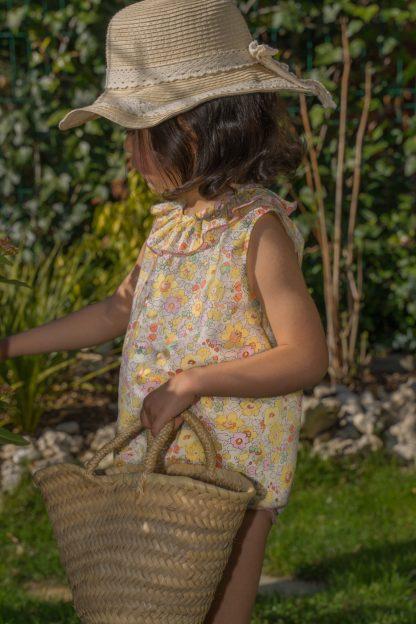 Niña en jardín vestida con blusa sin mangas de flores liberty amarillo, rosa y verde.