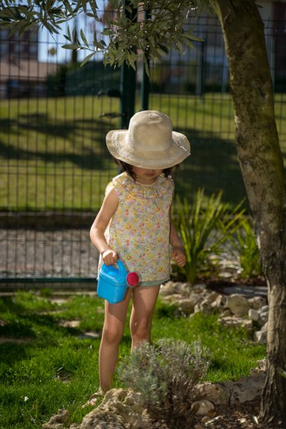 Niña en jardín vestida con blusa sin mangas de flores liberty amarillo, rosa y verde y bombacho verde a juego.